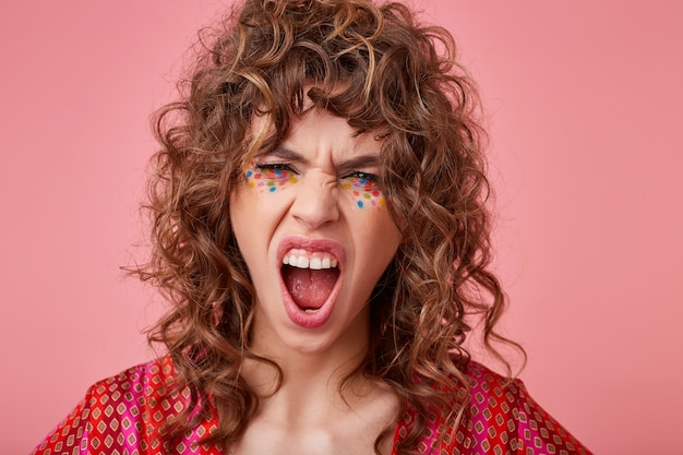 Angry young curly brunette female with festive makeup screaming violently with wide mouth opened and frowning her face, posing in colored patterned top