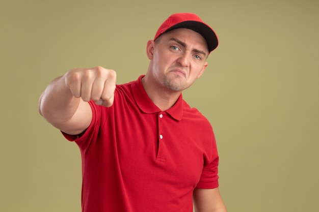 オリーブグリーンの壁に隔離されたカメラで拳を差し出す制服と帽子を身に着けている怒っている若い配達人