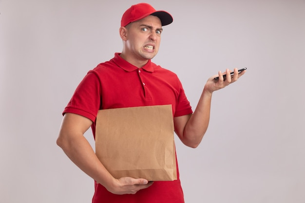 Сердитый молодой курьер в униформе с кепкой держит бумажный пакет продуктов с телефоном, изолированным на белой стене