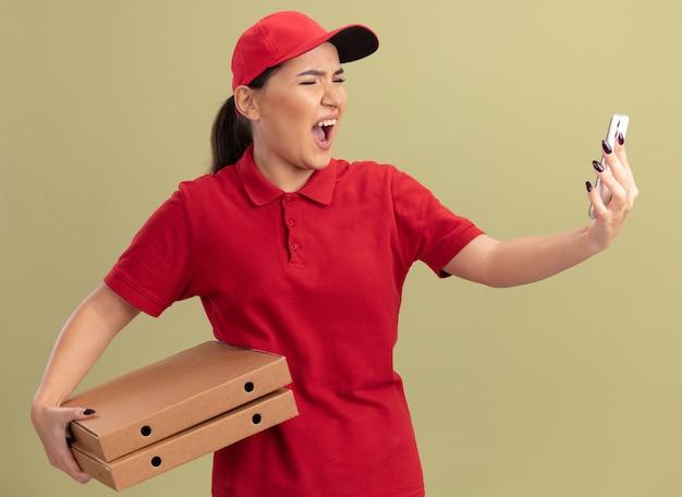 Сердитая молодая женщина-доставщик в красной форме и кепке держит коробки для пиццы, глядя на свой смартфон, крича с агрессивным выражением лица, стоя над зеленой стеной