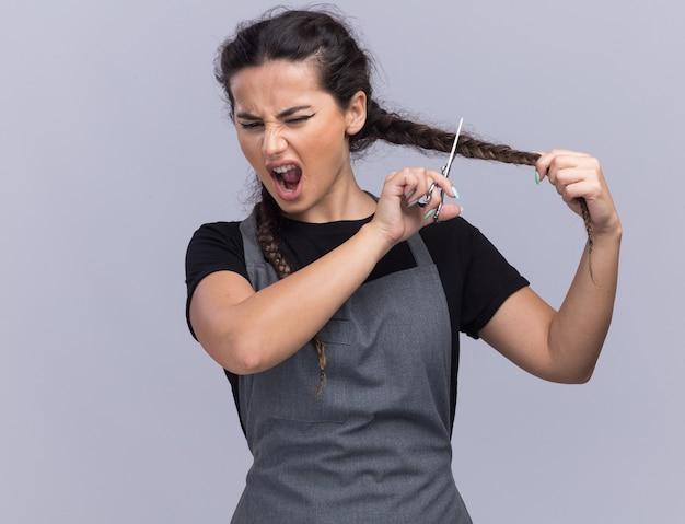 Сердитая молодая женщина-парикмахер в униформе стрижки волос изолирована на белой стене