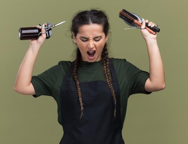 Сердитая молодая женщина-парикмахер в униформе поднимает инструменты парикмахера, изолированные на оливково-зеленой стене