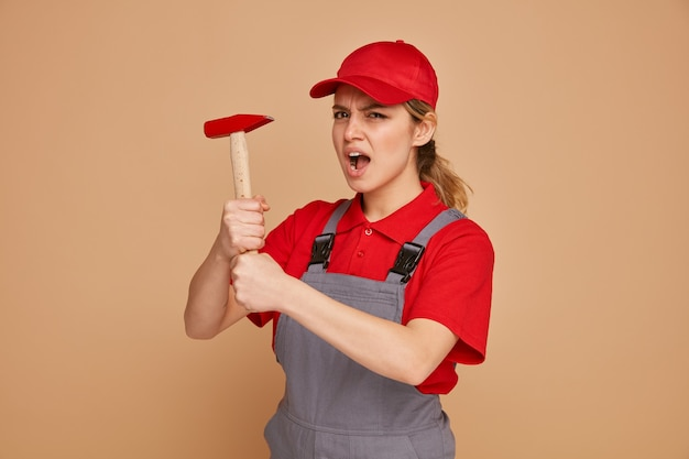 유니폼과 모자를 들고 망치를 입고 화가 젊은 여성 건설 노동자