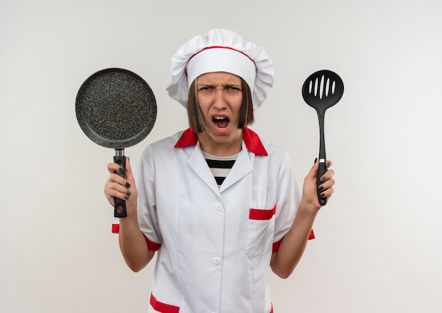 Angry young female cook in chef uniform holding spatula and frying pan looking isolated on white