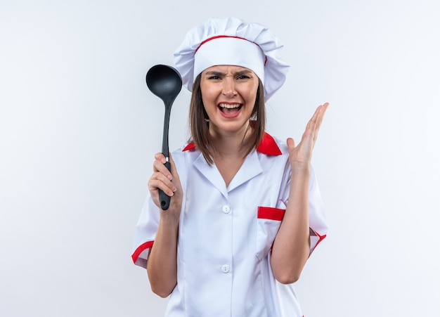Angry young female cook wearing chef uniform holding ladle isolated on white background