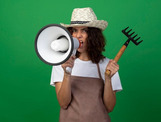 Arrabbiato giovane giardiniere femminile in uniforme che indossa cappello da giardinaggio tenendo il rastrello parla sull'altoparlante