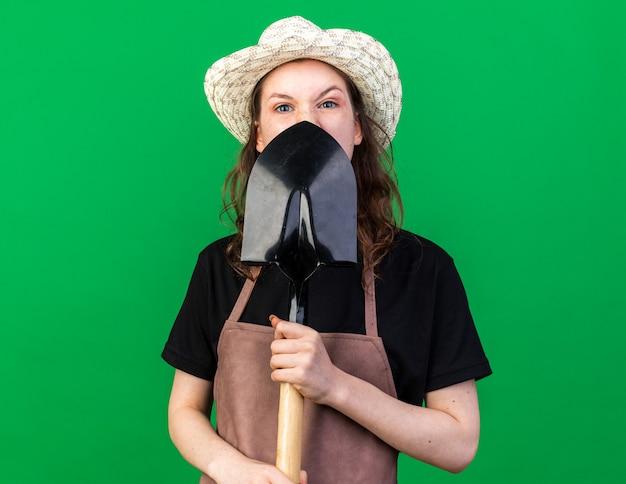 스페이드로 얼굴을 덮은 원예 모자를 쓴 화난 젊은 여성 정원사