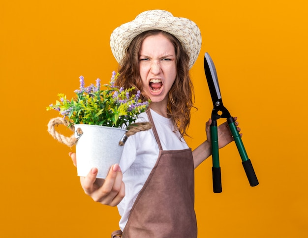 Angry young female gardener wearing gardening hat holding flower in flowerpot with pruning shear