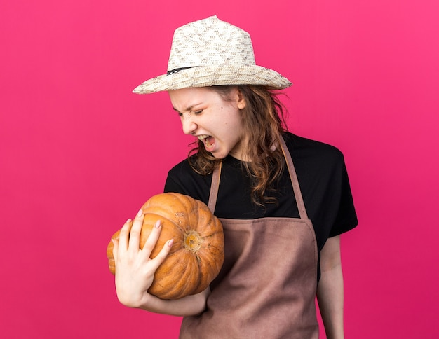 Angry young female gardener wearing gardening hat holding and looking at pumpkin