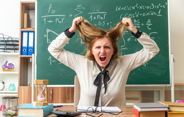 Una giovane insegnante arrabbiata si siede al tavolo con materiale scolastico afferrato i capelli in classe