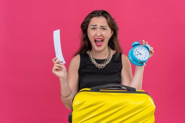 Сердитая молодая женщина-путешественница в черной майке держит будильник и билет на красной стене