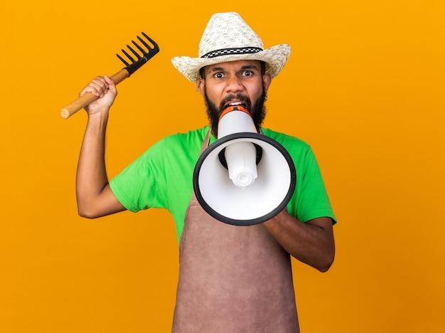 Angry young gardener afro-american guy wearing gardening hat holding rake speaks on loudspeaker