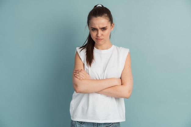 怒っている若い女の子が胸に腕を組んだ