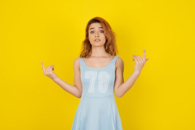 Ragazza arrabbiata in vestito sulla parete gialla