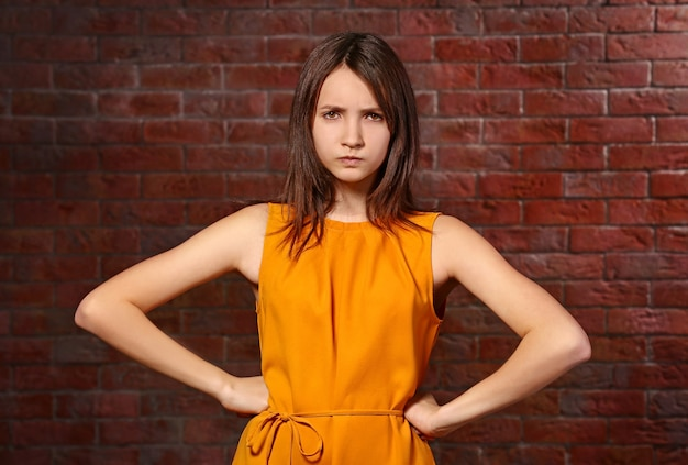 Angry young girl posing on brick background