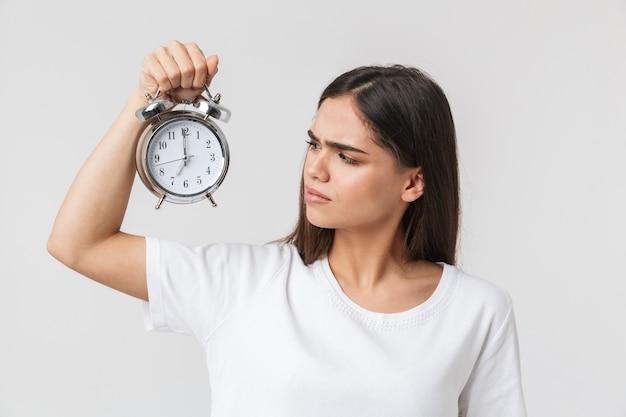 성 난 어린 소녀에 고립 된 흰색 서, 알람 시계를 보여주는