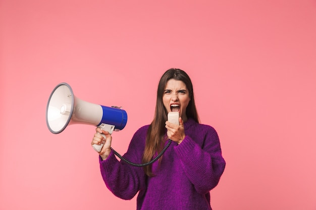 Сердитая молодая девушка в свитере стоит изолированно над розовым и кричит в динамик