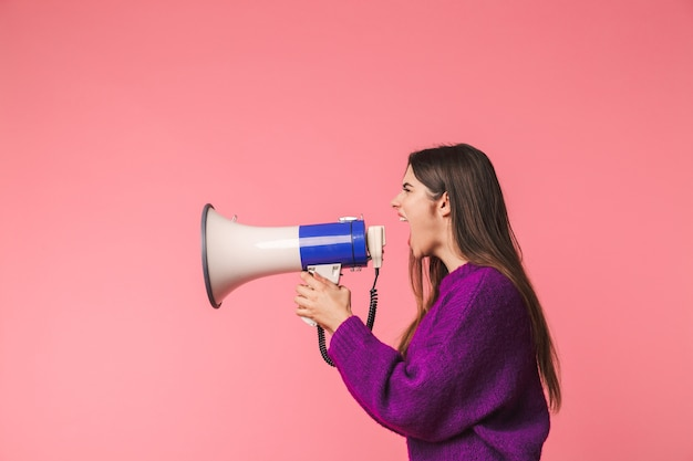 Angry young girl wearing sweater standing isolated over pink, shouting in a speaker