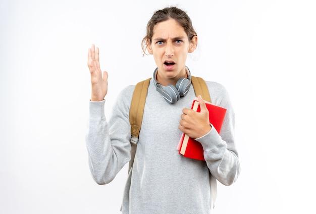 白い壁に隔離された本を保持している首にヘッドフォンとバックパックを身に着けている怒っている若い男の学生