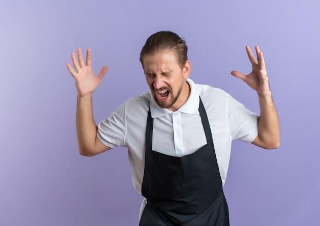 紫色で隔離の目を閉じて制服を上げる手を身に着けている怒っている若いハンサムな理髪師