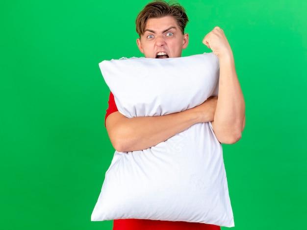 Злой молодой красивый блондин больной мужчина держит подушку, глядя в камеру сзади, сжимая кулак, изолированные на зеленом фоне с копией пространства