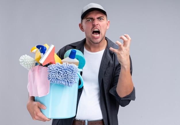 白い壁に隔離されたクリーニングツールのバケツを保持しているtシャツとキャップを身に着けている怒っている若いハンサムなクリーニング男