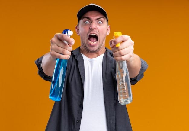オレンジ色の壁に隔離された正面にスプレーボトルを差し出すtシャツとキャップを身に着けている怒っている若いハンサムな掃除人