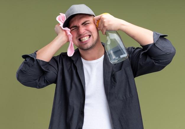 オリーブグリーンの壁に隔離された顔の周りにスプレーボトルでぼろきれを保持しているtシャツとキャップを身に着けている怒っている若いハンサムなクリーニング男