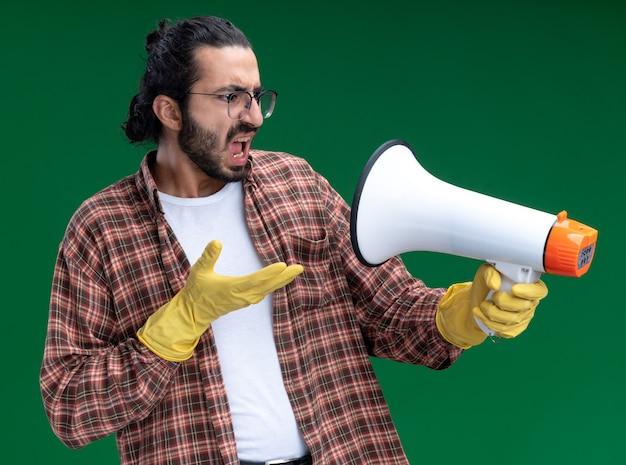 Злой молодой красивый уборщик в футболке и перчатках держит и указывает рукой на громкоговоритель, изолированный на зеленой стене