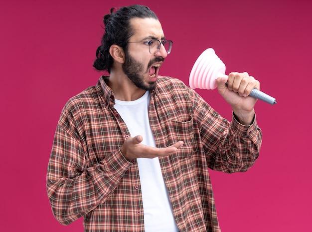 Arrabbiato giovane bel ragazzo delle pulizie che indossa t-shirt holding e guardando lo stantuffo isolato sulla parete rosa