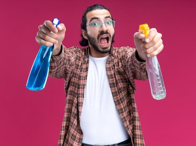 ピンクの壁に隔離された正面にスプレーボトルを差し出すtシャツを着て怒っている若いハンサムな掃除人