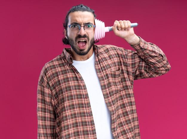 ピンクの壁に隔離された顔にプランジャーを置くtシャツを着て怒っている若いハンサムなクリーニング男