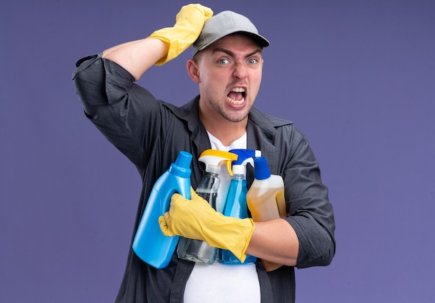 Angry young handsome cleaning guy wearing t-shirt with cap and gloves holding cleaning tools putting hand on head isolated on purple wall