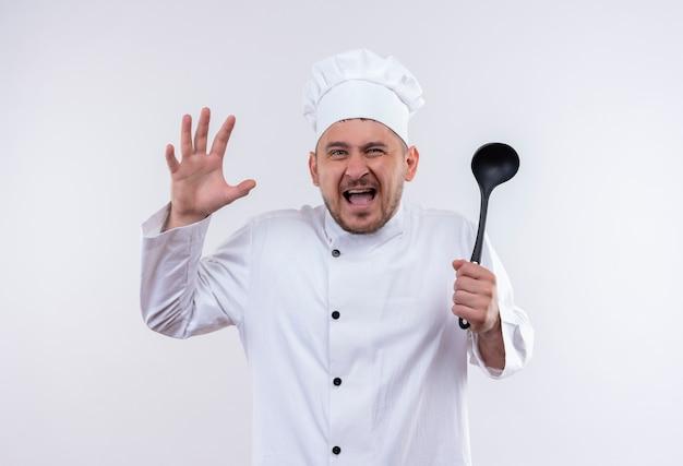 Giovane e bello cuoco arrabbiato in uniforme da chef che tiene mestolo con la mano alzata sul muro bianco isolato