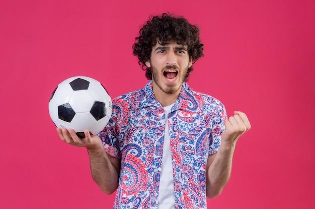 Giovane uomo riccio bello arrabbiato che tiene pallone da calcio con il pugno chiuso sullo spazio rosa isolato