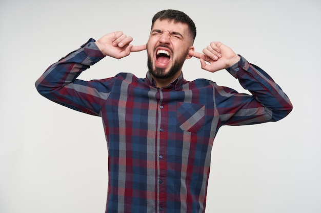 Angry young handsome dark haired bearded male with short haircut covering his ears and screaming loud with wide mouth opened, being annoyed because of loud sounds, isolated over white wall