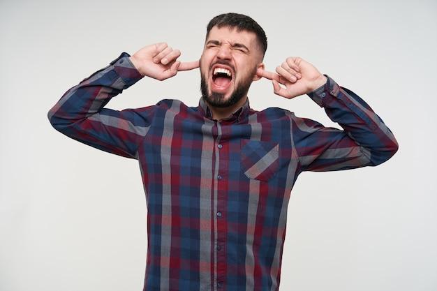Arrabbiato giovane maschio barbuto bello dai capelli scuri con taglio di capelli corto che copre le orecchie e urla ad alta voce con la bocca larga aperta, essendo infastidito a causa di suoni forti, isolato sopra il muro bianco