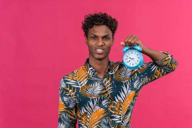 Злой молодой красивый темнокожий мужчина с вьющимися волосами в рубашке с принтом листьев держит синий будильник и показывает время