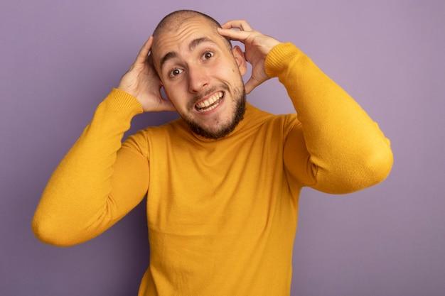 보라색 벽에 고립 된 머리 뒤에 손을 잡고 화가 젊은 잘 생긴 남자