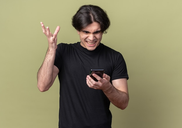 Angry young handsome guy wearing black t-shirt holding and looking at phone isolated on olive green wall