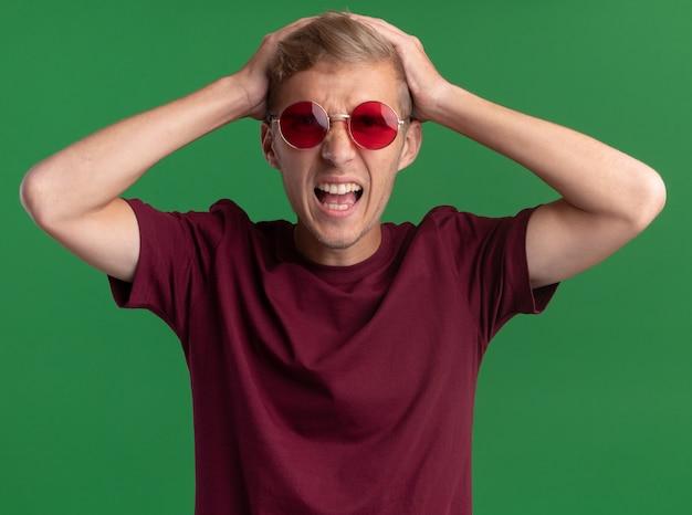 Злой молодой красивый парень в красной рубашке и очках схватился за голову, изолированную на зеленой стене