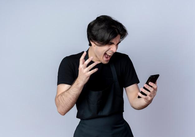 균일 한 잡고 흰색 배경에 고립 된 전화를보고 화가 젊은 잘 생긴 남성 이발사