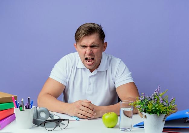 파란색 배경에 고립 된 학교 도구로 책상에 앉아 화가 젊은 잘 생긴 남자 학생