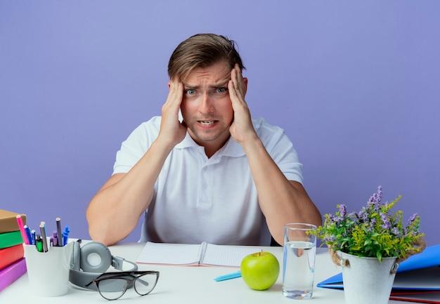 파란색 배경에 고립 이마에 손을 댔을 학교 도구로 책상에 앉아 화가 젊은 잘 생긴 남자 학생