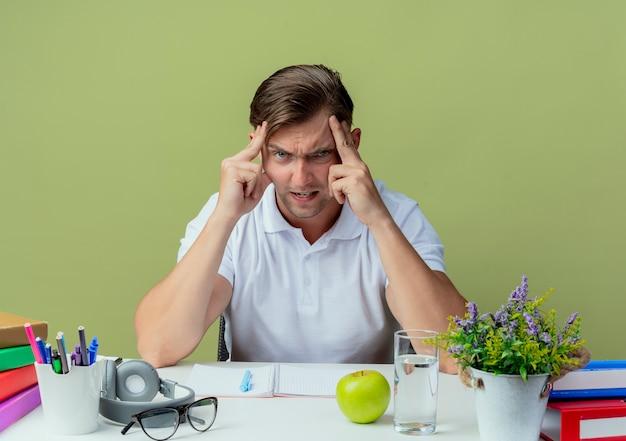 올리브 그린에 고립 된 이마에 손을 댔을 학교 도구로 책상에 앉아 화가 젊은 잘 생긴 남자 학생