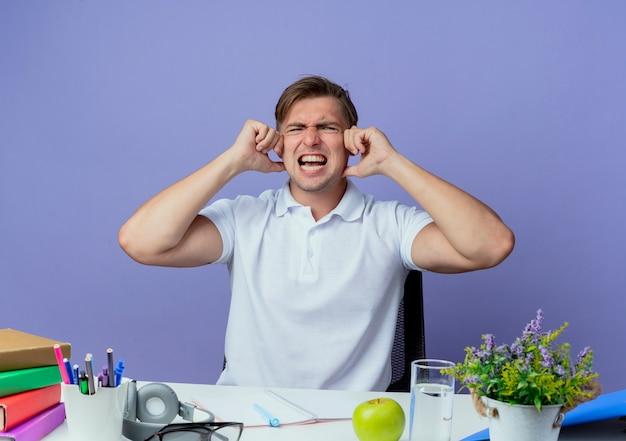 Giovane studente maschio bello arrabbiato che si siede allo scrittorio con gli strumenti della scuola ha coperto le orecchie con la mano isolata sulla parete blu