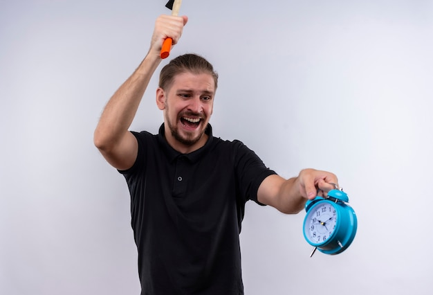 Angry young handsome man in black polo shirt with a hammer going to break alarm clock in his hand with aggressive expression on face standing over white background