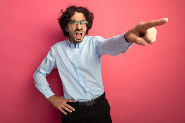 ピンクの壁で隔離された側を見て、腰に手を置いて眼鏡をかけている怒っている若いハンサムな男