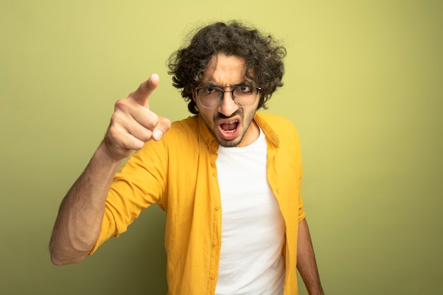 怒っている若いハンサムな男は、オリーブグリーンの壁に隔離された正面を見て、指している眼鏡をかけています