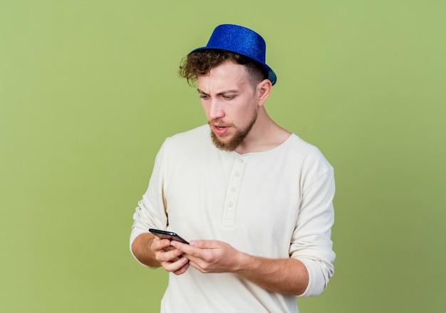 파티 모자를 쓰고 올리브 녹색 벽에 고립 된 휴대 전화를보고 화가 젊은 잘 생긴 파티 남자